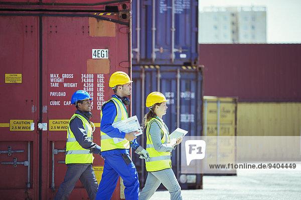 Geschäftsleute und Arbeiter in der Nähe von Frachtcontainern