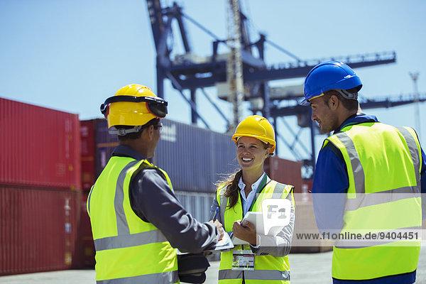 Geschäftsleute und Arbeiter sprechen in der Nähe von Frachtcontainern