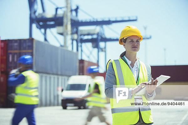Geschäftsfrau mit digitalem Tablett in der Nähe von Frachtcontainern