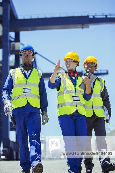 Arbeiter und Geschäftsleute im Gespräch beim Ladekran