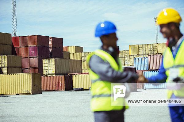 Arbeiter und Geschäftsmann beim Händeschütteln in der Nähe von Frachtcontainern