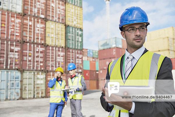 Geschäftsmann mit digitalem Tablett in der Nähe von Frachtcontainern