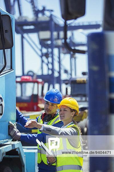 Kauffrau und Arbeiterin bei der Untersuchung eines Lastkraftwagens in der Nähe eines Ladekrans