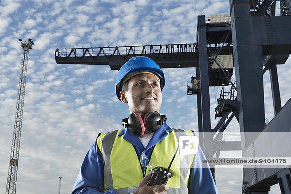 Arbeiter lächelt in der Nähe des Ladekrans