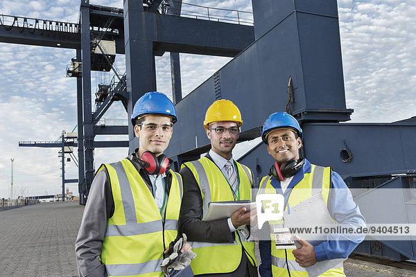 Arbeiter und Geschäftsleute lächeln in der Nähe von Ladekranen