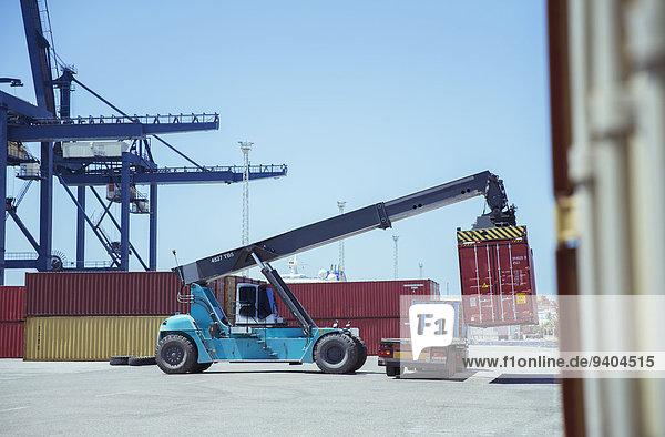 Kran hebt Frachtcontainer auf Lkw