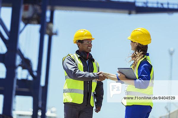 Arbeiter und Geschäftsmann beim Händeschütteln am Ladekran