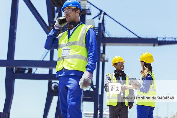 Arbeiter mit Walkie-Talkie am Ladekran