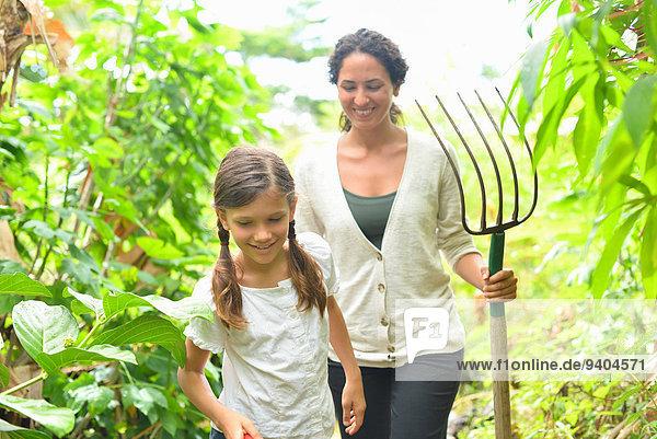 Mädchen und Frau mit Gartengabel durch Pflanzen im Gewächshaus gehen