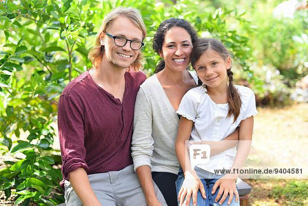 Porträt von lächelnden Eltern mit Tochter auf Bank im Garten sitzend