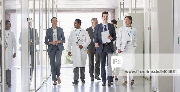 Wissenschaftler und Geschäftsleute  die im Flur spazieren gehen