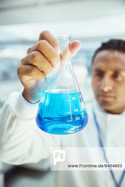 Wissenschaftler untersucht Probe im Becherglas im Labor