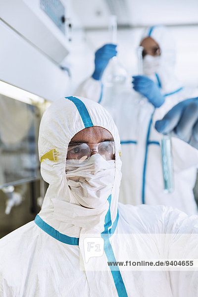 Wissenschaftler im Clean Suit untersucht Reagenzglas im Labor