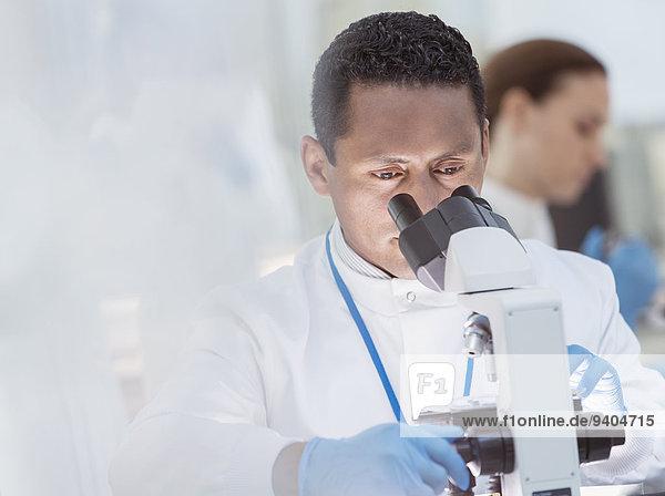 Wissenschaftler untersucht Probe unter dem Mikroskop im Labor