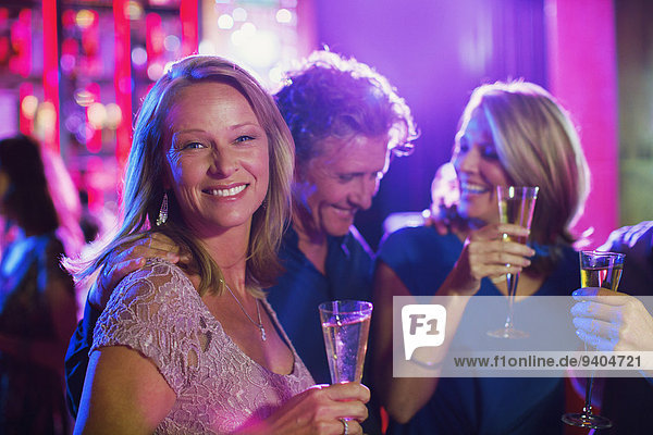 Friends with champagne flutes having fun in nightclub