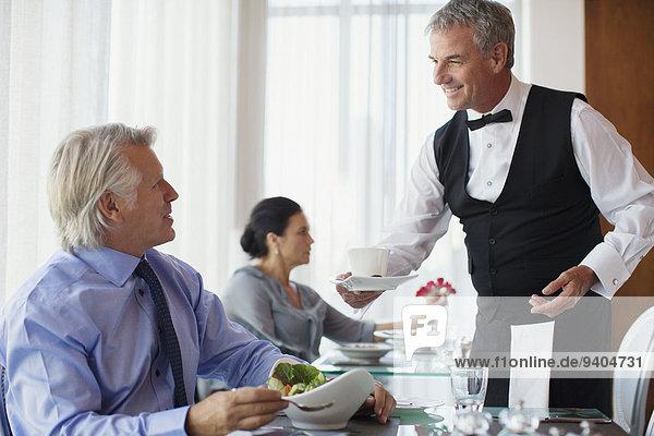 Kellner serviert eine Tasse Kaffee an einen reifen Mann  der am Tisch im Restaurant sitzt.