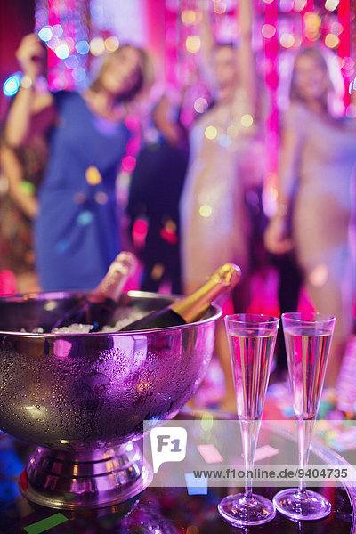 Champagne bottles in ice bucket and champagne flutes in nightclub  people dancing in background