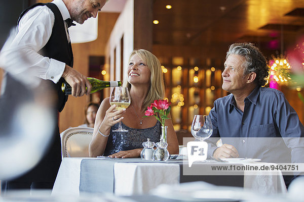 Mature couple sitting at restaurant table  waiter pouring white wine into woman's glass