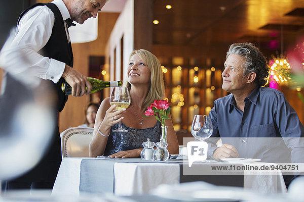 Ein reifes Paar sitzt am Restauranttisch  der Kellner gießt Weißwein in das Glas der Frau.