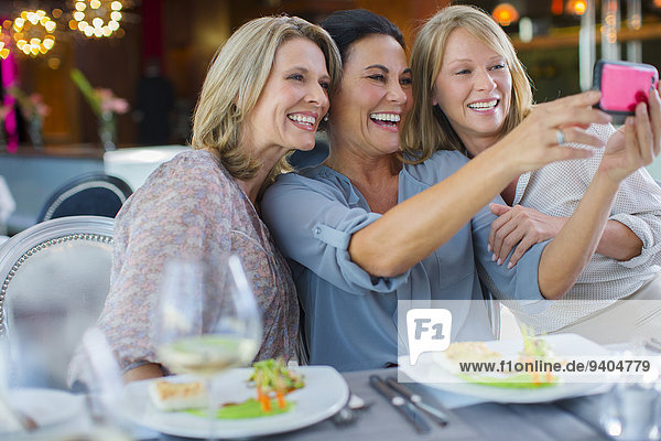 Female friends taking selfie in restaurant