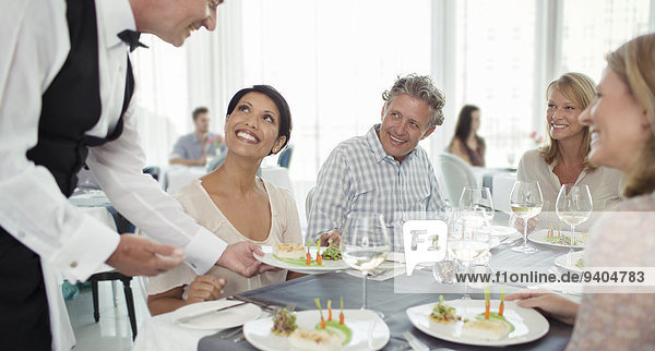 Waiter serving fancy dish to woman sitting at restaurant table