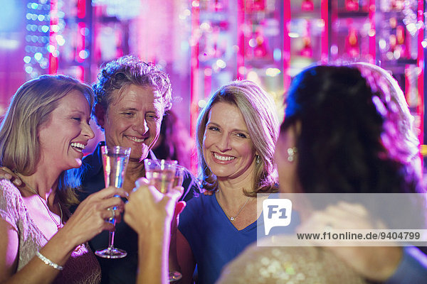 Smiling mature people toasting with champagne flutes in nightclub