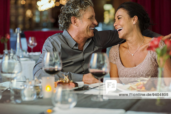 Happy mature couple sitting at restaurant table  wineglasses in foreground