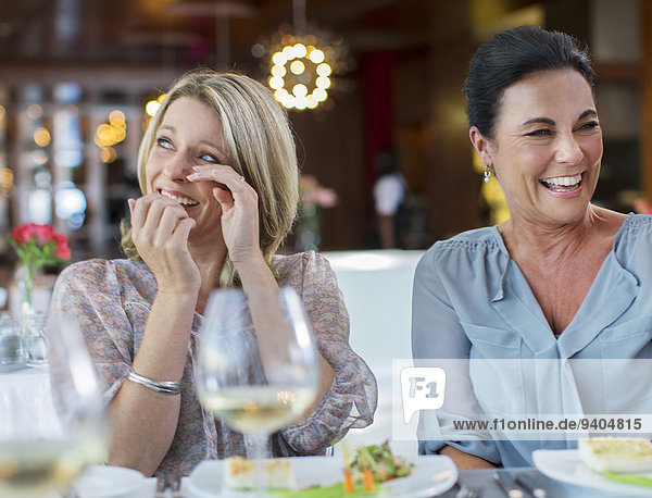 Women laughing at table in restaurant