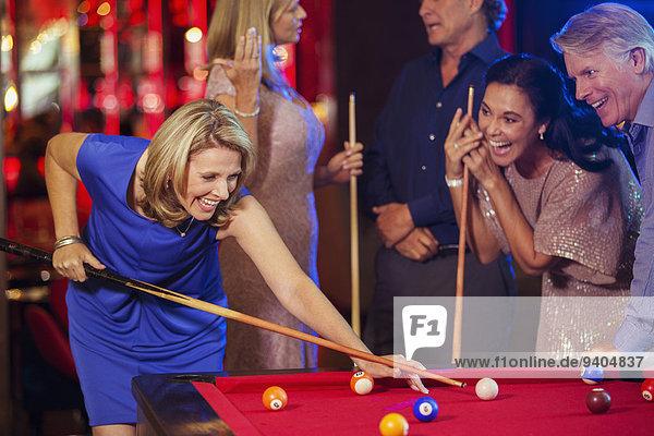 Freunde spielen Pool im Nachtclub