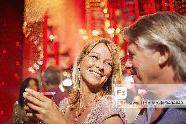 Reife Paare lächeln im Nachtclub