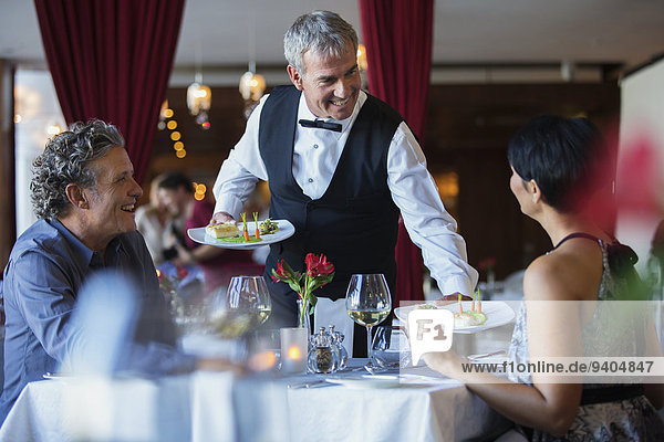 Smiling waiter serving fancy dishes to mature couple sitting at table in restaurant