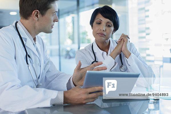 Ärzte besprechen die Behandlung des Patienten am Schreibtisch mit Hilfe eines digitalen Tabletts.