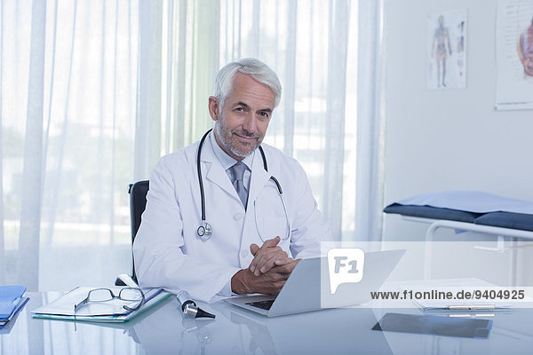 Portrait of smiling mature doctor sitting at desk with laptop in office