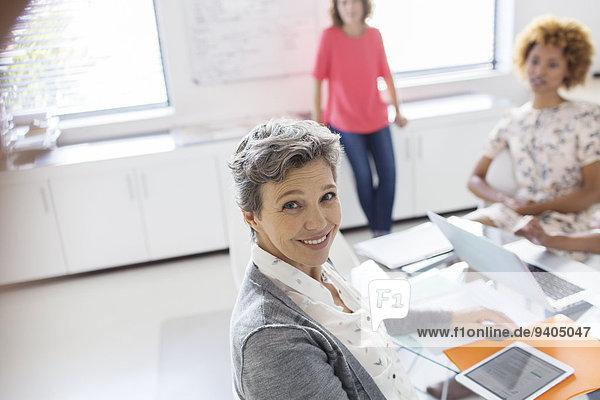 Porträt der lächelnden reifen Geschäftsfrau am Schreibtisch im Büro