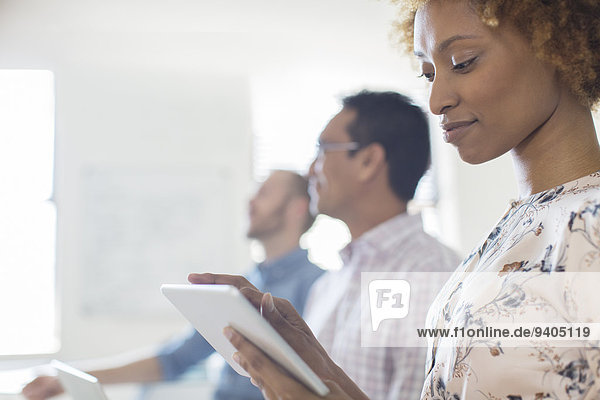 Porträt einer Frau mit Tablette im Büro  Kollegen im Hintergrund