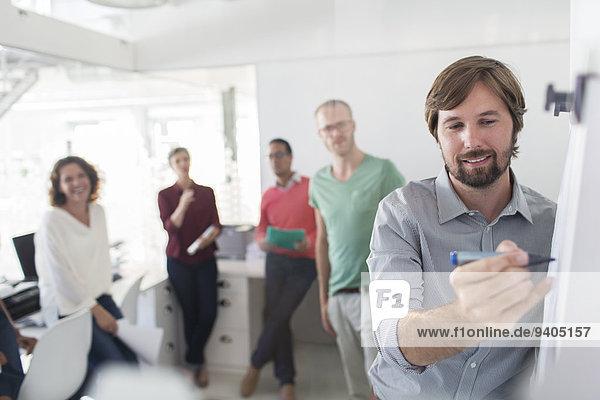 Gruppe von Leuten  die sich im Büro treffen  Mann schreibt auf Flipchart