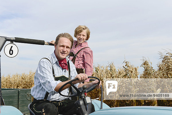 Father and son on tractor in cornfield
