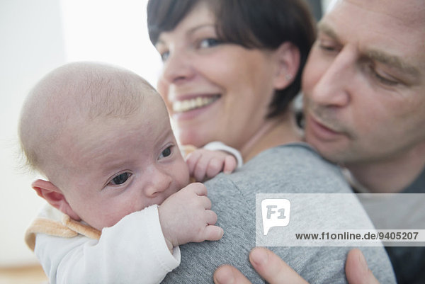 Family holding baby boy  smiling  close up