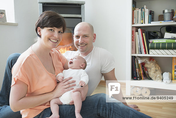 Portrait of parents with baby boy in living room  smiling