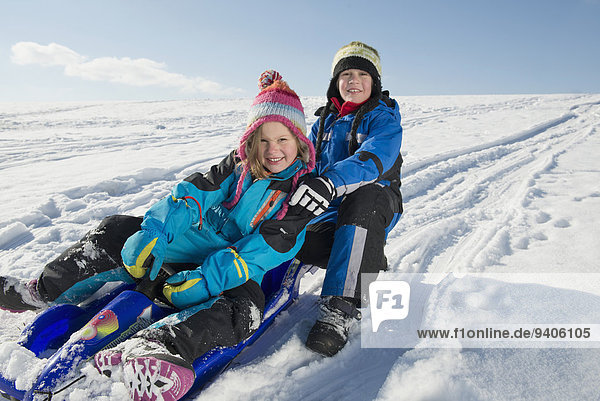 Brother and sister sledging down hill  smiling