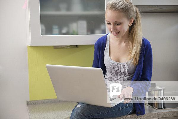 benutzen Jugendlicher Notebook lächeln Küche Mädchen