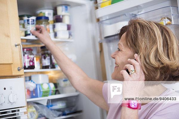 Senior Senioren Frau lächeln offen Kühlschrank