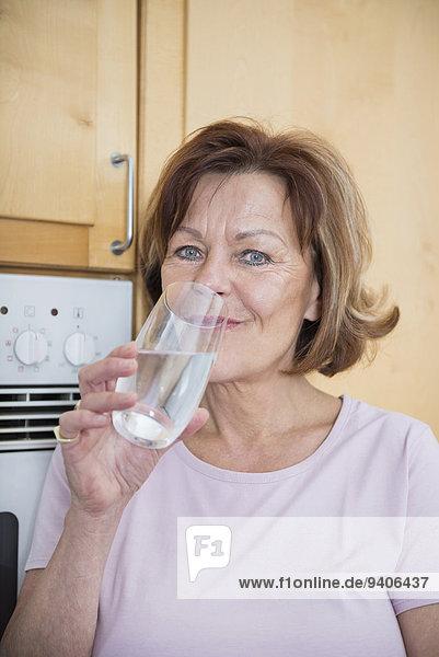 Senior Senioren Wasser Portrait Frau Glas lächeln Küche