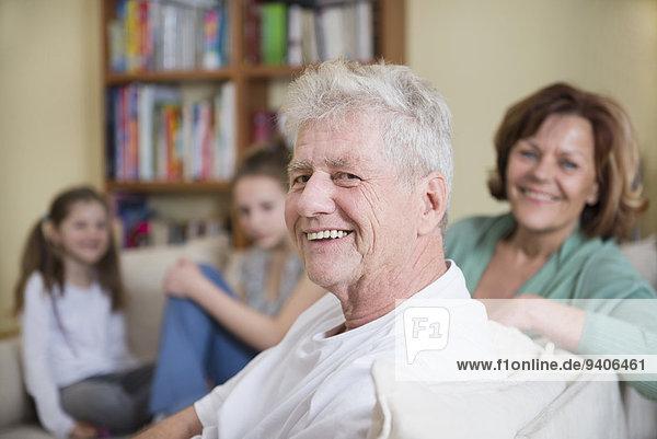 sitzend Portrait lächeln Großeltern Enkeltochter Couch