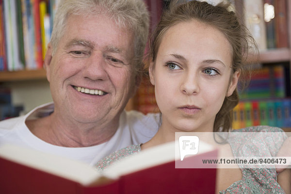 Grandfather and granddaughter reading book on couch in living room  smiling