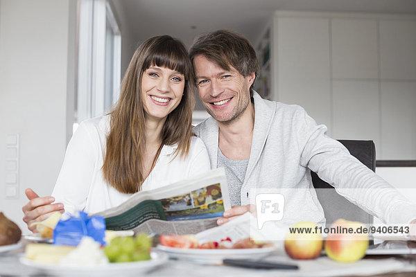 Zusammenhalt Portrait lächeln Frühstück Zeitung vorlesen