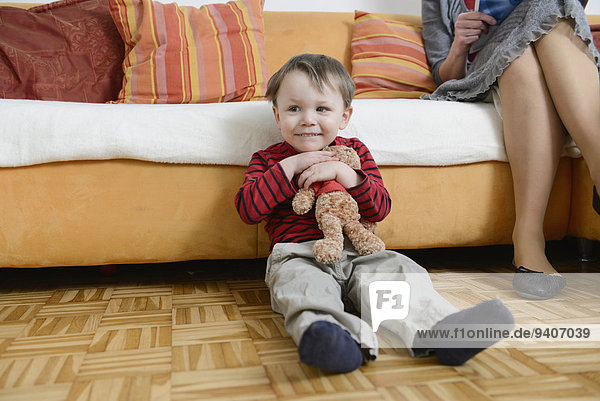 sitzend Boden Fußboden Fußböden lächeln Junge - Person Teddy Teddybär