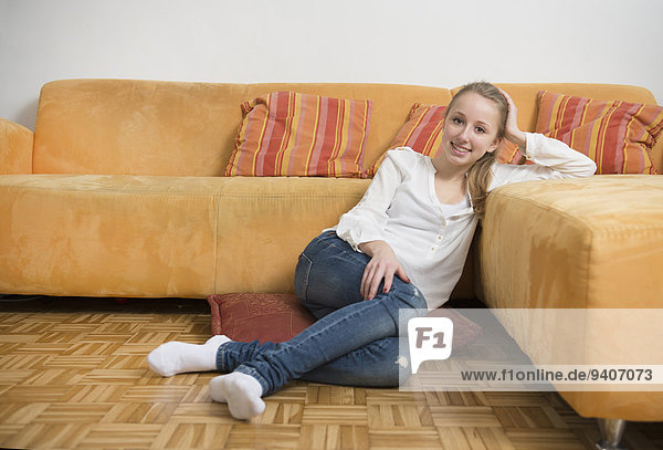 Portrait of teenage girl sitting on floor in living room  smiling