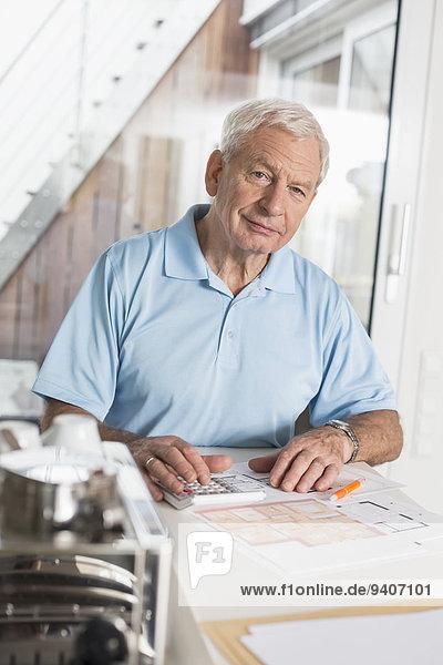 Interior zu Hause Senior Senioren benutzen Mann Taschenrechner