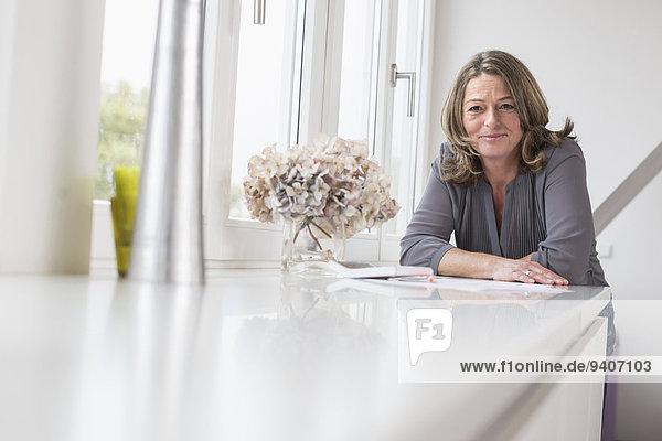 angelehnt Portrait Frau lächeln reifer Erwachsene reife Erwachsene Tisch